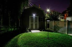 wireless flood light installed above shed doors beams lighting