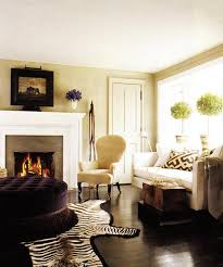 cozy living room space beige tan paint wall color upholstered velvet purple round tufted ottoman with fringe cowhide zebra rug fireplace antique art black beige living room