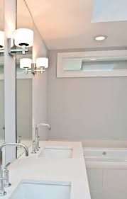 transom window above bathtub area to allow natural light into a bathroom located in the interior allowing natural light fill