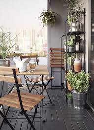 a small balcony furnished with a foldable table and three foldable chairs all in solid balcony furnished small