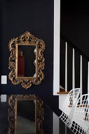 dining room table mirror top: bold black dining room features a black wall lined with a gold rococo mirror facing an antiqued mirrored top dining table lined with white bertoia chairs