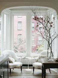 a table in front of two comfy chairs provides a nice place to get a cup bay window furniture
