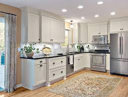 kitchen moldings: closeup of light rail skirt trim on painted linen shaker cabinets with gray marble backsplash and
