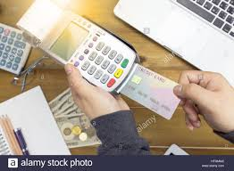 cashier hand holding a credit card over edc machine or credit card cashier hand holding a credit card over edc machine or credit card terminal calculator and glasses a credit card over ese bank notes