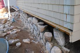 stone patio installation: we are creating a stone staircase a new foundation wall and a new blue stone patio at the back of the house
