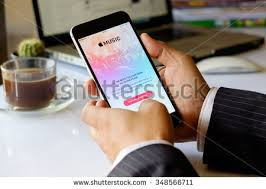 a man hand holding screen apple music app showing on iphone 6 plus in his office apple thailand office