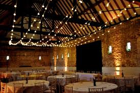 strings of warm white festoon lights in rustic wedding barn barn wedding lights