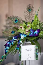 day orchid decor: purple wedding table decor with peacock feathers and orchid decorations