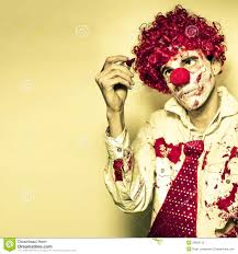 horror clown writing halloween message in blood stock photo horror clown writing halloween message in blood