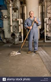 industrial setting stock photos industrial setting stock images male caucasian in blue custodian janitor overalls in factory setting including boiler pipes