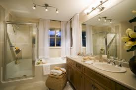 bathroom idea in small space with corner bathtub and shower and wooden double vanities sink also wicker basket and unique ceiling and wall lights and ceiling wall shower lighting