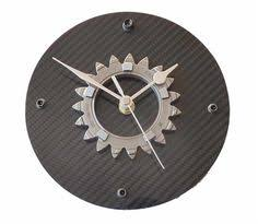 wall clock made using a race used 4th gear from a honda f1 racecar mounted to very high quality real carbon fiber carbon fiber tape furniture