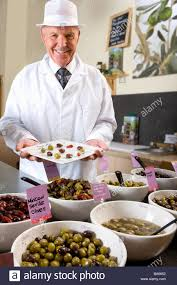 s clerk displaying specialty olives stock photo royalty s clerk displaying specialty olives