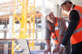 what s the difference between a construction bid and an estimate construction workers using laptop on construction site