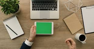 green office desk. business man using tablet scrolling checking information on with green screen hands office desk