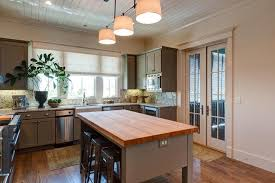 kitchen island granite top sun: cottage kitchen features a shiplap ceiling over grey cabinets paired with granite countertops and backsplash