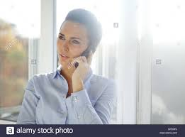 business woman standing in a bright office while talking on her mobile phone looking away beautiful caucasian female model beautiful bright office