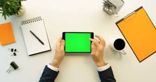 green office desk. business man using tablet device with green screen on white office desk orange details male hand scrolling pages zooming computer