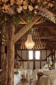 crystal wedding chandelier with a fairy light canopy at the beautiful loseley park tithe barn wedding lighting by oakwood events ltd flowers by the barn wedding lighting