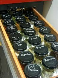 A drawer of glass jars of spices with lids with the name of the spice.