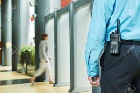 security guard controlling indoor entrance gate stock photo stock photo security guard controlling indoor entrance gate