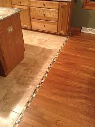 kitchen floor tiles small space: interior hardwood to tile floor transition with small mosaic tiles as the divider a kitchen set and kitchen island tile to wood floor transition ideas