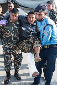 us department of defense photo essay  a nepalese army soldier and airport security guard help an earthquake victim into an ambulance at