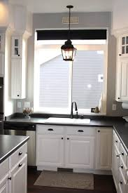 above kitchen sink lighting ideas using candle shaped led bulbs inside pendant lantern light fixtures also black cup pulls and cast iron knobs above kitchen sink lighting