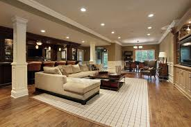 huge man cave with sectional sofa bar recessed lighting and hard wood floor basement lighting layout