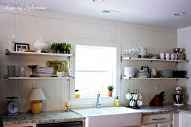 white kitchen windowed partition wall:  open kitchen shelves ideas with countertop and glass window