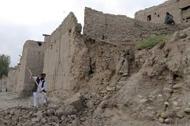 powerful earthquake shakes south asia newshour a man clears rubble in jalalabad after part of his house collapsed during