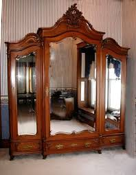 antique french victorian walnut armoirethis antique victorian triple door armoire with beveled glass mirrors and carved crest is french it was made circa antique english country armoire circa 1830s