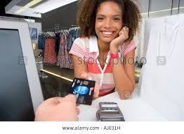 young w by counter in clothes shop smiling portrait shop stock photo young w by counter in clothes shop smiling portrait shop assistant holding out credit card