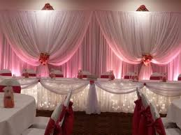 beautiful fabric head table backdrop with pink uplighting beautiful color table uplighting