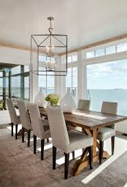long wood dining table: beautiful dining room boasts a white capiz chandelier hanging over a reclaimed wood trestle dining table lined with linen dining chairs with nailhead trim