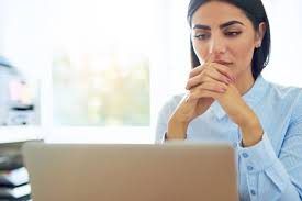 137 questions to ask about your digital employer branding business w a serious look on her face glances at her laptop screen in an