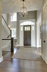gorgeous entryway with high ceilings tall front door dark wood floors and open stairway brilliant foyer chandelier ideas