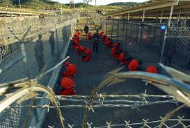 editor humanities core research blog page  detainees in orange jumpsuits sit in a holding area at camp x ray of naval