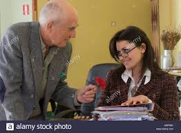 busy young w in office working her annoying boss older stock photo busy young w in office working her annoying boss older male colleague trying to seduce her red carnation