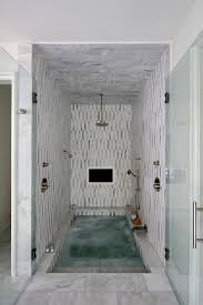 spa bathroom showers: stunning spa shower boasts white and gray marble tiles and ceiling fitted with a built in tv and a circular rain shower head and sprayer aimed over a sunken