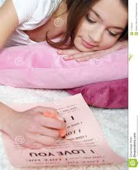 girl lies on a bed and writes the love letter - girl-lies-bed-writes-love-letter-17752520