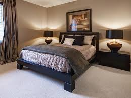 a heavy platform bed anchors this beige bedroom featuring soft lighting black nightstands and silk beige bedroom furniture