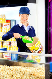 worker serving popcorn in bucket at cinema concession counter gallery of concession stand worker
