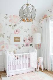 adorable pink and white girls nursery clad in jolie wallpaper on the upper walls and wainscoted lower walls features a jenny lind floor lamp lighting a adorable pink chandelier