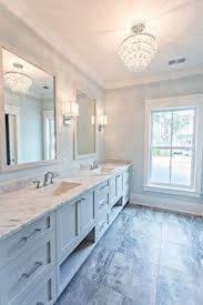 bathroom features gray shaker vanity: traditional bathroom with alcove filled with gray shaker vanity accented with round nickel pulls topped with a white and grey marble counter framing a