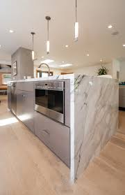 calacatta marble kitchen waterfall: marble waterfall countertops hide stainless steel appliances in this kitchen photo courtesy of sara cozolino view details