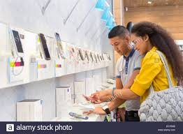 store assistant helping female customer in phone store stock photo stock photo store assistant helping female customer in phone store