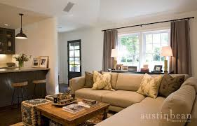 gorgeous living room with beige linen sectional sofa topped with black and brown geometric pillows beside kelly wearstler bengal bazaar pillows in front of beige sectional living room
