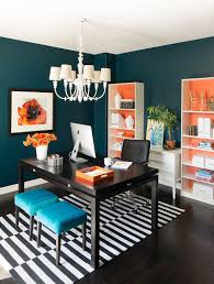 bright home office with orange accent and black desk with blue chair plus black arcm chair also white chandelier and black and white rug with dark flooring bright home office design