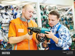 s assistant at work male hardware store worker helps to s assistant at work male hardware store worker helps to choose drill or perforator to